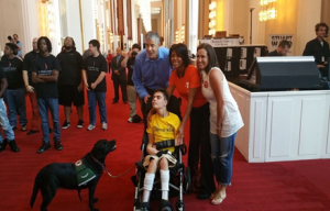 Secretary Duncan and friends posing with a boy in a wheelchair and his assistant dog.