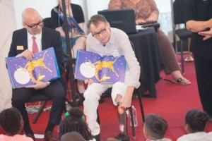 Two men reading from a book titled Giraffes Can't Dance by Giles Andreae and illustrator Guy Parker-Rees about Gerald the Giraffe who did not dance like the rest of the animals.