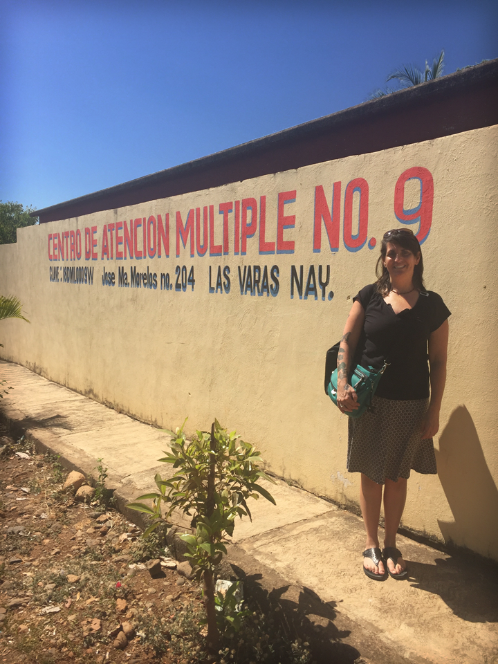 Lillian Durán standing in front of a school