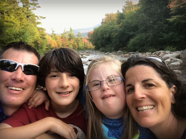 Carrie Woodcock and her family posing in front of a lovely rural stream