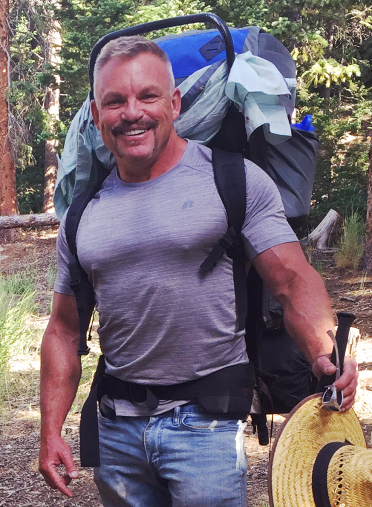 Will Eiserman with a back pack in the woods