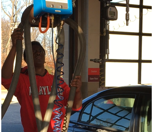 Kenneth Singletary, lubricating a car.